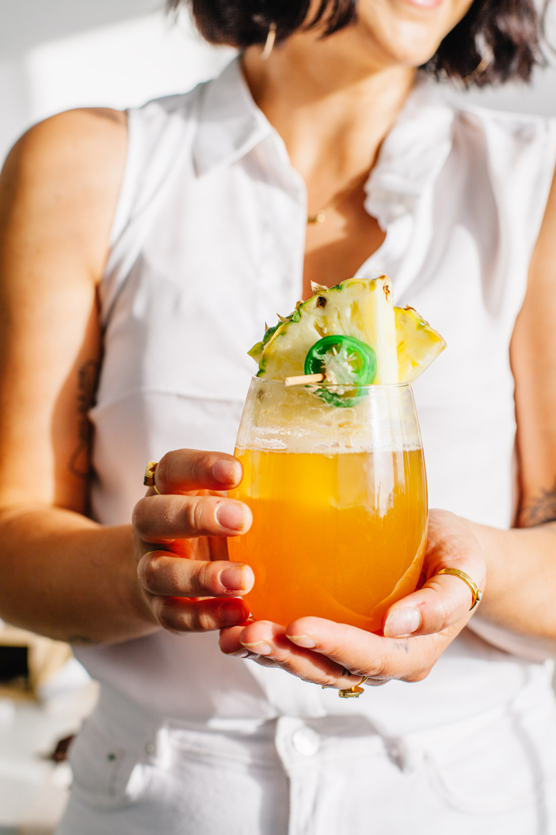 hands holding pineapple mocktail