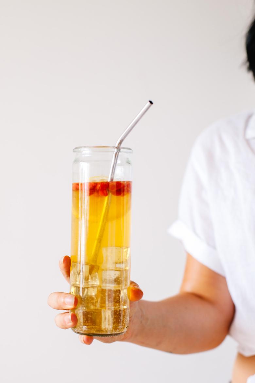 Hand holding a glass of goji berry sparkling lemonade
