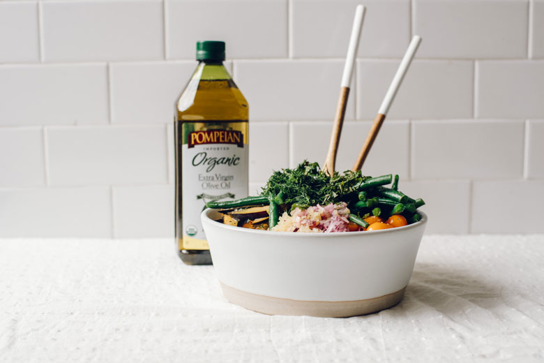 a bowl with quinoa salad in it and a bottle of Pompeian Organic Extra Virgin Olive Oil in the background