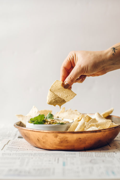 hand dipping chip into queso