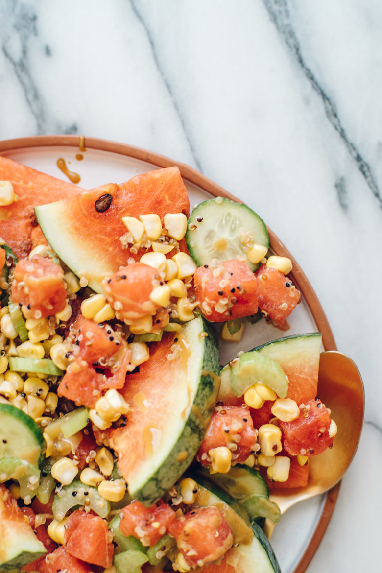 close up of a watermelon salad with corn, cucumber, quinoa, celery and a sweet mustard dressing