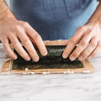 person rolling a sushi roll in nori