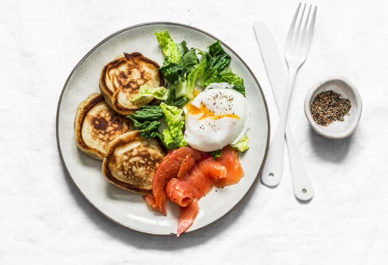 a smoked salmon breakfast plate with salad, poached eggs, and pancakes