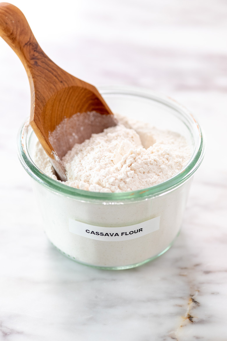 jar of cassava flour with a wooden scoop in it