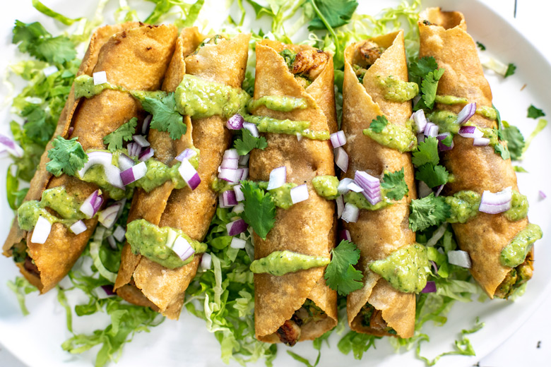 close up of taquitos topped with salsa verde, cilantro and red onion