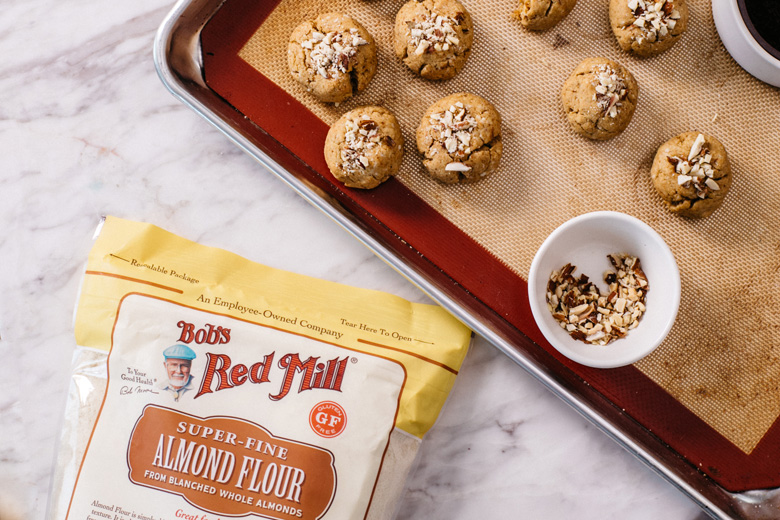 half of a sheet pan with almond cookies sits in the upper right side of the frame, a bag of Bob's Red Mill almond flour peeks in to the bottom left part of the frame