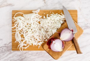 A wood cutting board sits in the middle of a marble counter, on it are dice onions and sliced onions. In the bottom right corner sits a red onion cut in half with a large chefs knife