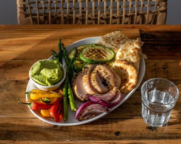 a grilled dinner board with grilled chicken, grilled flatbread, and grilled vegetables such as asparagus, zucchini, mini pepper, and onion sit on a white plate. A small white bowl of avocado-feta dipping sauce is also on the plate. In the background is a chair and there is a small glass of water in front of the plate.