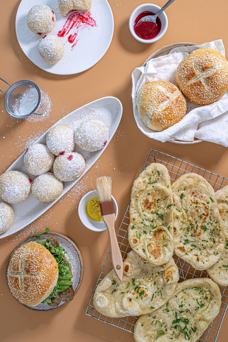 a large spread of flatbreads, jelly donuts, and rolls or hamburgerbuns