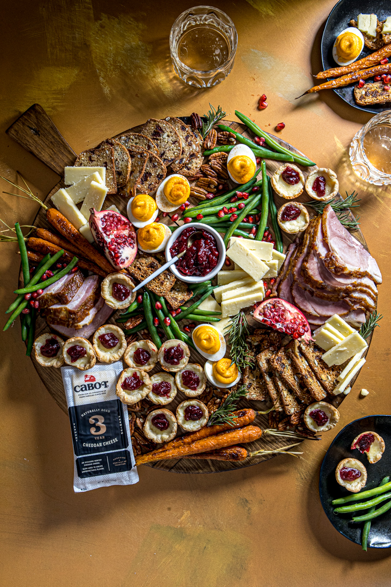 a huge holiday dinner board with crackers, Cabot 3 Year Aged cheddar slices, cranberry sauce, blanched green beans, roasted carrots, ham, deviled eggs, and aged cheddar-cranberry bites!