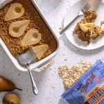 Pear-Ginger Oatmeal bake in a white casserole dish, with one slice cut out on a plate in the upper right corner. There are two cups of coffee casting light onto the speckled countertop. A bag of Bob's Red Mill Rolled Oats sits in the bottom right corner of the counter.