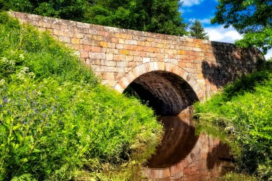Give Freely: A peaceful stream flowing under an old stone bridge.
