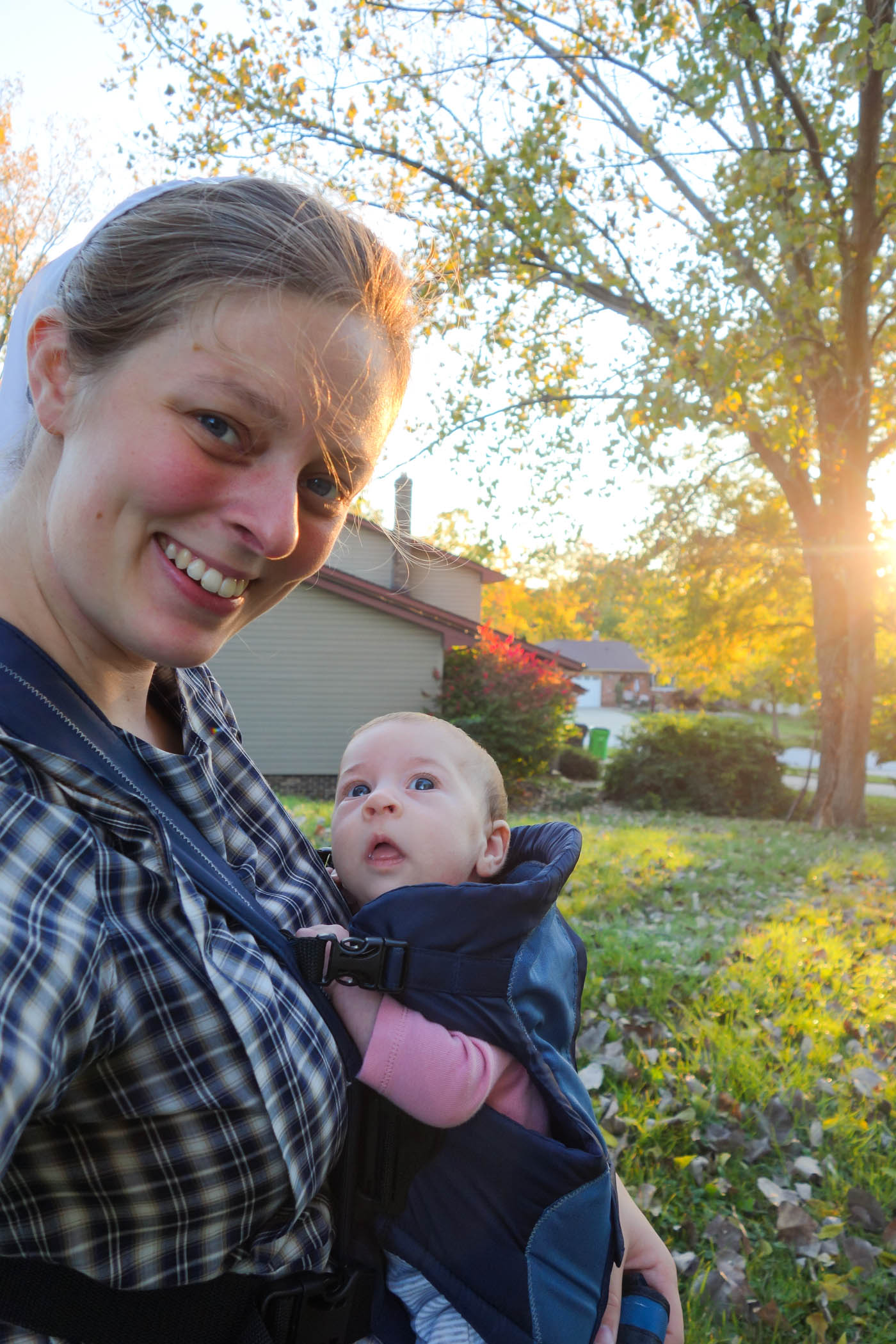 This is a picture of Briana carrying Hadassah on her chest in a baby carrier, golden sunlight streaming through a tree in the background.