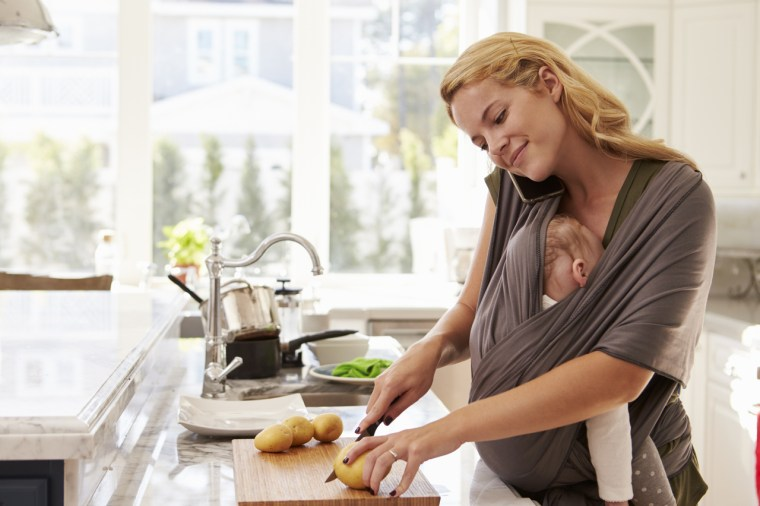 Mother multitasking: talking on phone while cooking and holding a baby