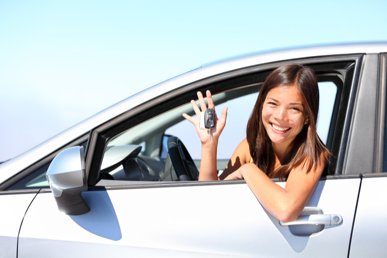 Woman in rental car holding car keys