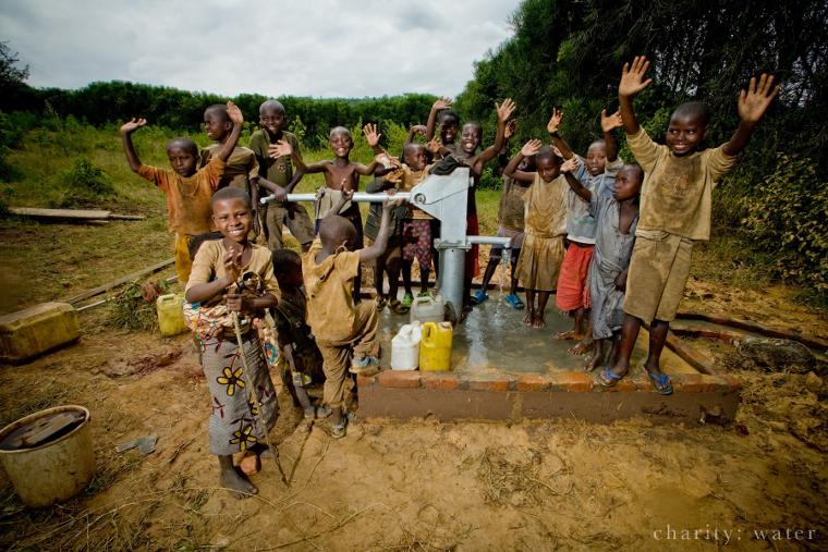 Rwandan children celebrating around charity: water well
