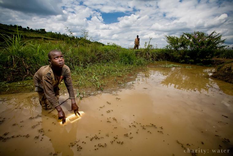 Rwandan collecting filthy water
