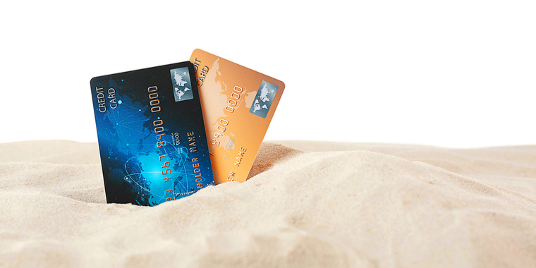 2 credit cards stuck in the sand