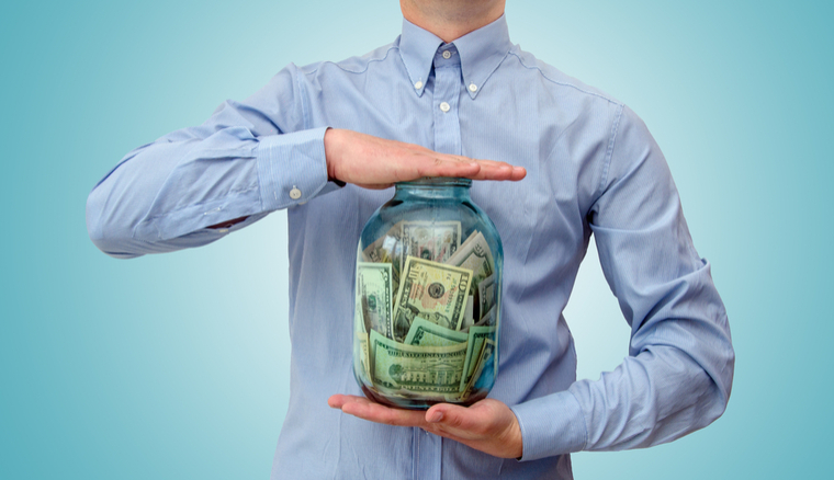 Man holding glass jar with money in it