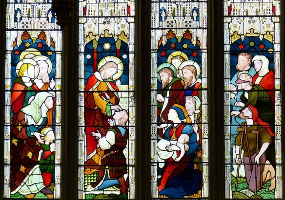 stained glass window depicting Jesus performing miracles