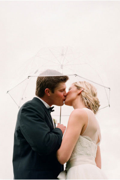 bride and groom under a clear umbrella