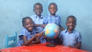 Four Bridge pupils with globe. Partnership Schools for Liberia.
