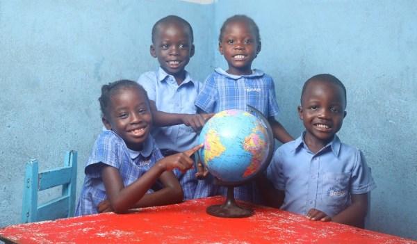 Four Bridge pupils with globe. Partnership Schools for Liberia.
