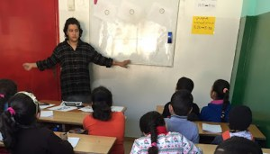 Teacher stands at whiteboard in front of children