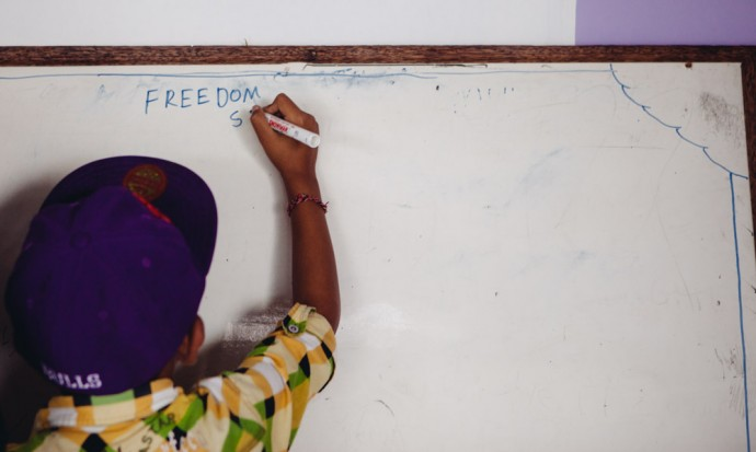 Boy writing Freedom on the white board
