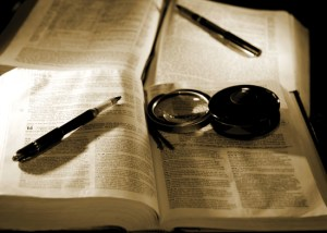 Christian bible study image in sepia tint and high contrast - two bibles with pens and a magnifying glass (shallow focus point on foreground pen, bible, and magnifying glass).