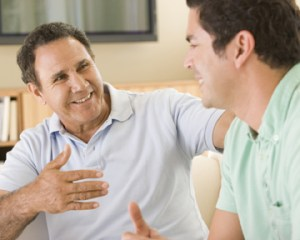 Two men in living room talking and smiling14351347