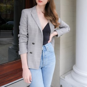 Girl wearing a grey plaid blazer, black body suit and blue Levi's Ribcage Straight Ankle Jeans standing on the steps of a buidling There is a column to her left. Minimalist outfit ideas, minimalist style, blazer inspiration, Business casual looks, fashion outfit of the day, less is more, quality over quantity.