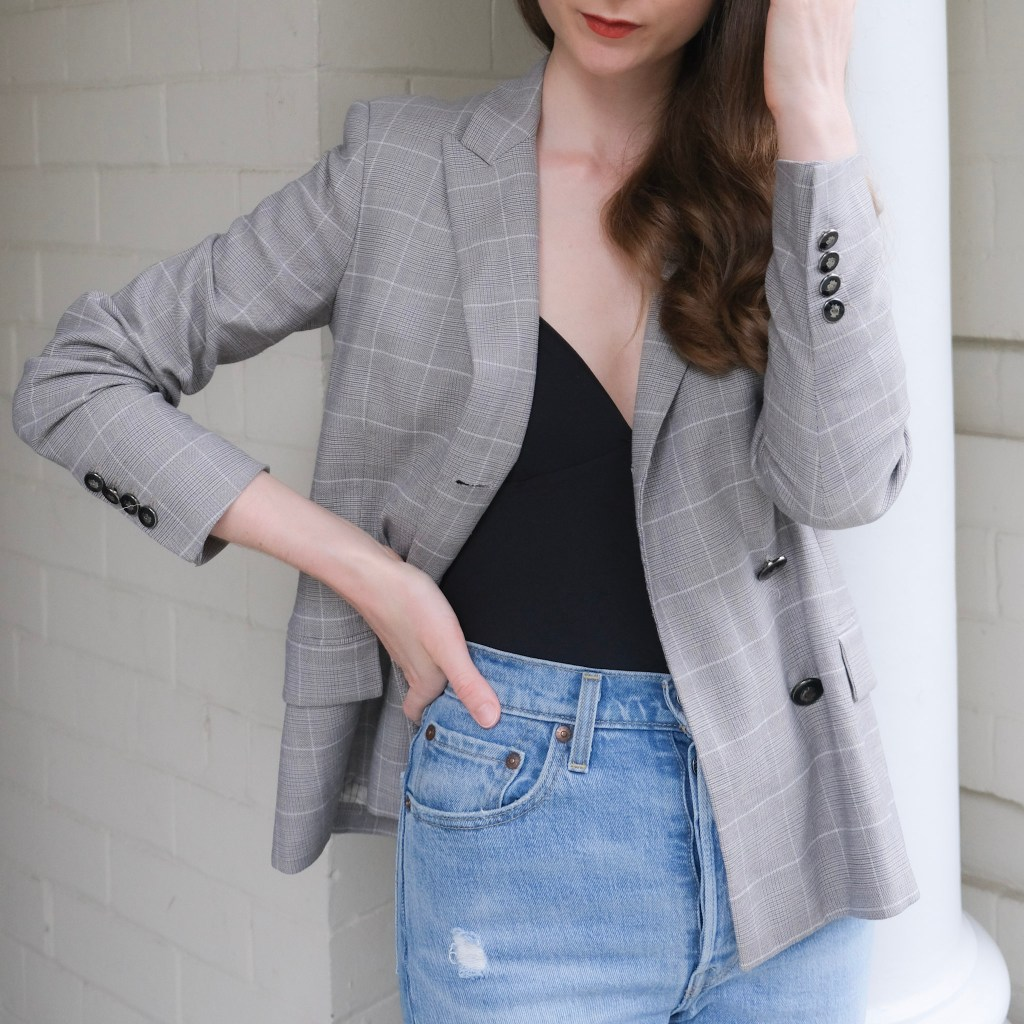 A girl standing outside a building wearing a grey blazer, Levi's ribcage straight ankle jeans, neutral pumps. Minimalist outfit inspiration, blazer style inspo, denim look, denim outfit