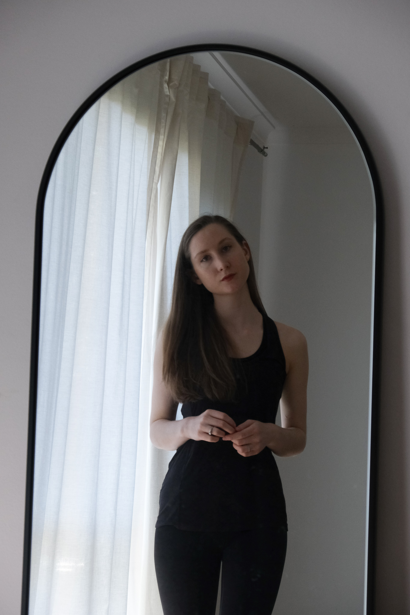 Girl standing in front of a mirror wearing Boody active wear tank top and Dharma Bums black 7/8 scallop leggings. Sustainable activewear review, minimalist active wear, sustainable brands