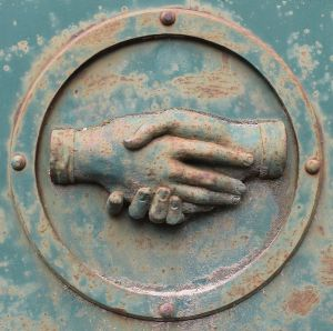 metal plaque depicting a handshake