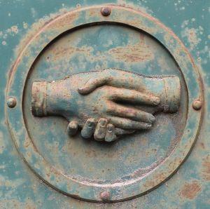metal plaque depicting a handshake