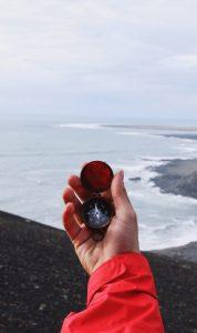 hand holding compass near coastline