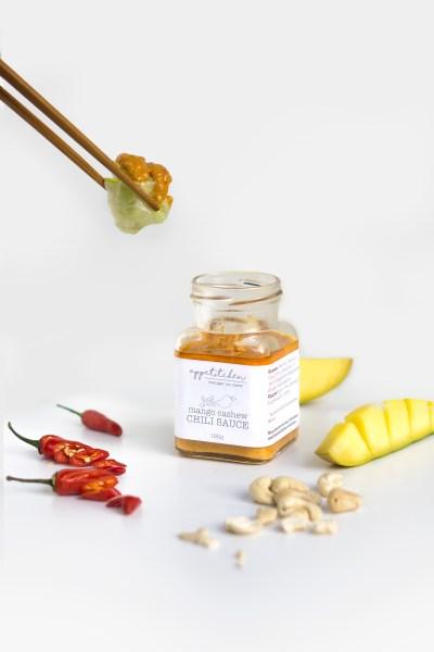 Stäbchen mit Sommerrolle über ein Glas Chili Sauce mit Mango und Cashew