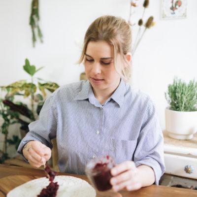 Frau bestreicht tortilla mit rote beete chutney