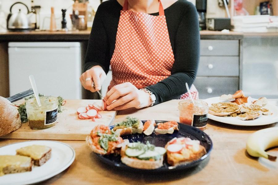 Frau schneidet Gemüse und belegt Brote