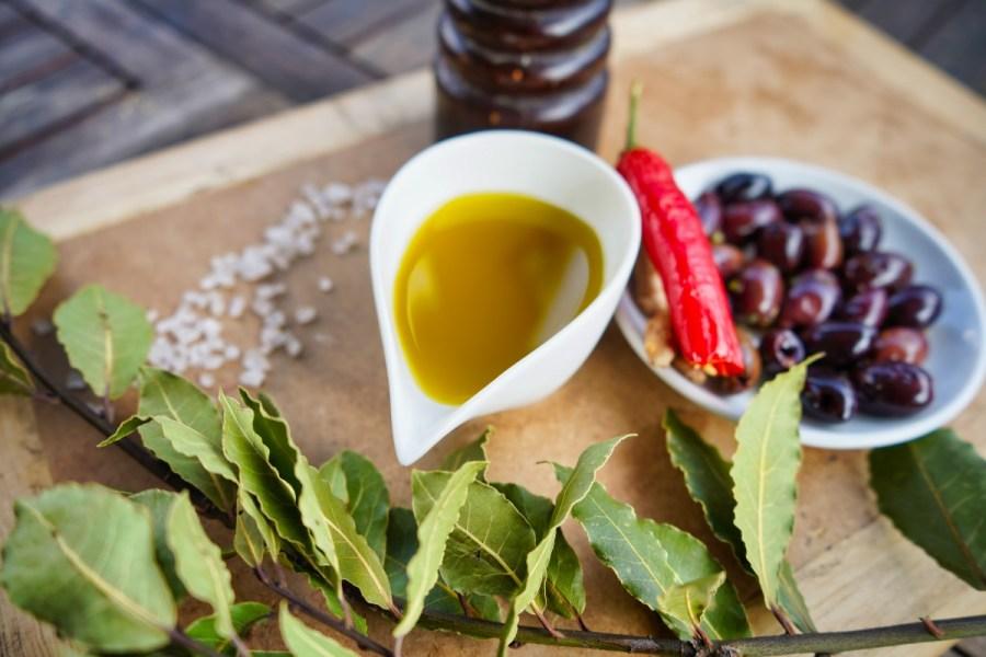 Vita verde Olivenöl in Schale mit Oliven und Blättern auf Brett