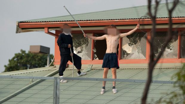 Youths  protesting on the roof of the Melbourne Youth Justice Centre in Parkville in March.