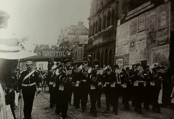 Photograph from a parade in 1900 showing the raised pedestrian walkway and the George and Railway Hotel in the background