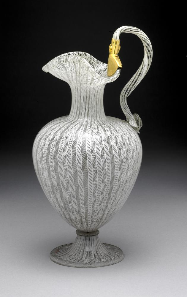 Ewer; glass; oviform body on narrow stem and bell-foot; narrow neck and trefoil mouth; arched handle terminating in animal mask; gilt metal plates where handle joins rim; ornamented throughout with vertical bands of white filigree.