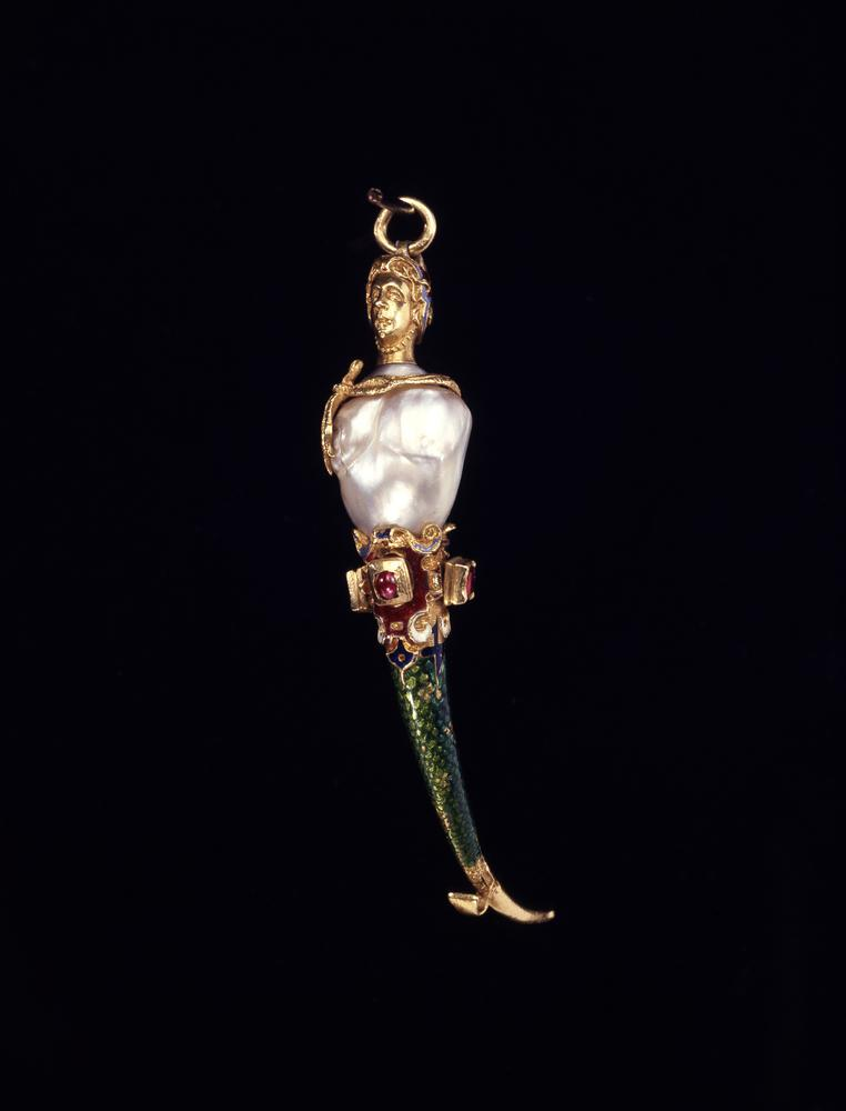 Gold and pearl toothpick pendant in the form of a mermaid. A large irregularly shaped 'baroque' pearl forms the torso of the mermaid and has been left totally in the round. The attached gold head, facing front, wears an elaborate head-dress of enamelled scrollwork, red and blue, terminating in a loop, through which a gold suspension ring is attached. The head-dress largely hides the hair, though tresses escape in the front and a bun projects at the back; it has a gold ribbon that passes under the chin of the mermaid. From the back of the head fall two thin strands of drapery in pounced gold which are looped around the line of the join in the pearl and tied in a loose knot or bow at one side so that the two ends fall over the mermaid's right breast.Below the 'baroque' pearl the lower part of the mermaid commences with a 'belt' of Renaissance scroll and strap-work cartouches in relief, enamelled in red, blue and white, and set with three rubies in raised gold collets; the two rubies on either side are table-cut in fine rectangular settings, but the central ruby is en cabochon and the simple setting appears to have been reworked.Below the 'belt' the scaly tail of the mermaid commences with a translucent green enamel covering the ever-diminishing engraved scale pattern as the tail narrows; the line where the scaly pattern of the tail begins at the top and ends at the bottom is very sharply delineated in a Mannerist mixture of curves and abrupt right angles. The final section of the tail is neither engraved nor enamelled; instead, the burnished gold tapers to a point, but at the junction with the end of the scaly pattern in the front of the tail a little gold hook or scraper with a double curve projects and extends upwards.