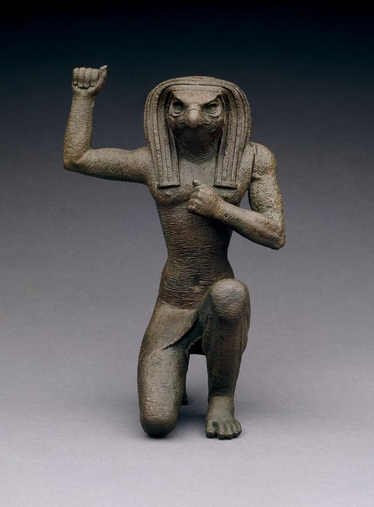 Sculpture from British Museum of falcon headed egyptian god horus on one knee with one fist raised and one to his chest