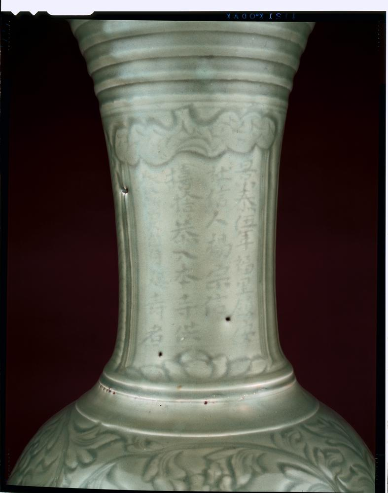Longquan porcelain vase with long neck, flared mouth and everted rim. The vase has grey-green glaze. There are concentric rings around the neck above overlapping leaves, lotus and peony scroll bands around the body, and overlapping lotus petals around the lower part. There is an inscription on the neck.