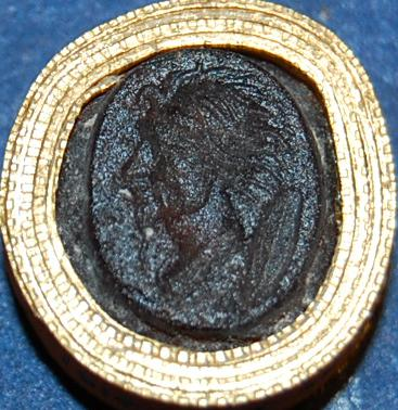 Oval brown glass paste intaglio: bearded head in profile to right.