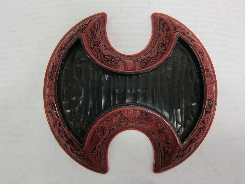 Dish (ingot-shaped). With figures and dragons. Made of carved red and black lacquer. Inscription. With lacquered wooden storage box.