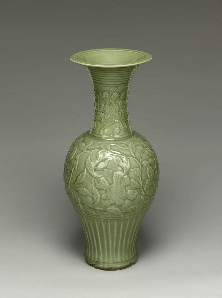 Longquan stoneware vase with long neck and flared mouth. The vase has grey-green glaze. There are carved petals around lower part of the exterior, concentric rings around the neck, and pomegranate scrolls around the body. There is an inscription around the lip.
